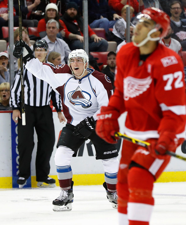 . Colorado Avalanche defenseman Tyson Barrie (4) celebrates a Nathan MacKinnon goal as Detroit Red Wings center Andreas Athanasiou (72) skates in the third period of an NHL hockey game Saturday, March 18, 2017, in Detroit. (AP Photo/Paul Sancya)
