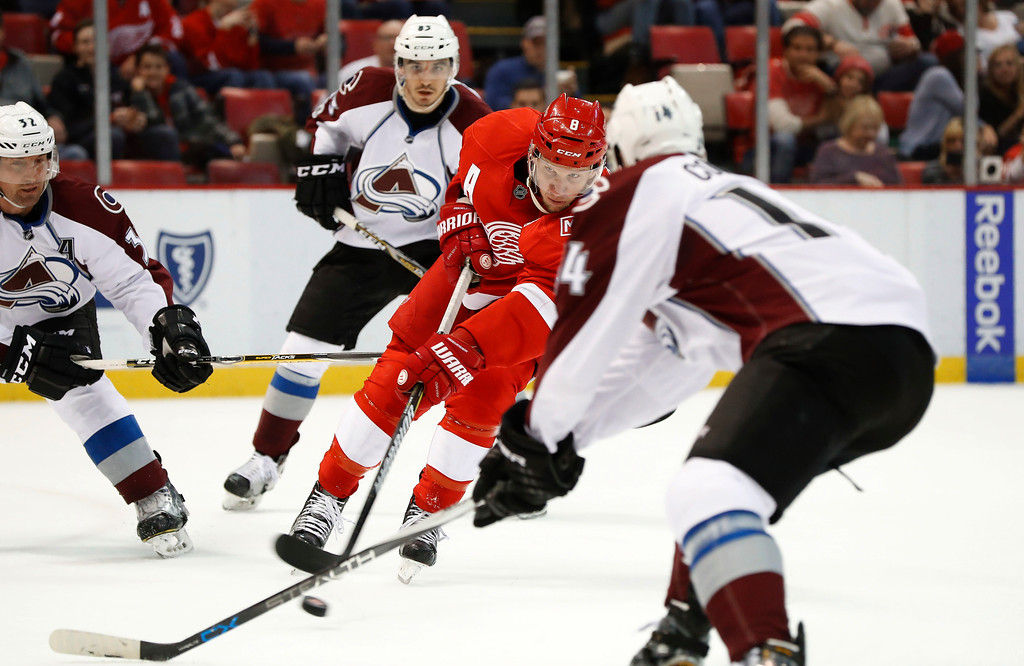 . Detroit Red Wings left wing Justin Abdelkader (8) shoots against Colorado Avalanche defenders in the second period of an NHL hockey game Saturday, March 18, 2017, in Detroit. Abdelkader scored on the shot. (AP Photo/Paul Sancya)