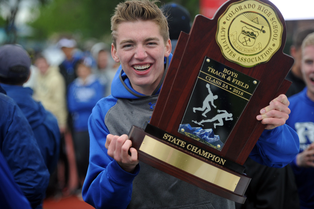 . Christian Fagerlin shows off Resurrection Christian\'s 2A state championship trophy on Saturday at Jeffco Stadium. (Sean Star/Loveland Reporter-Herald)