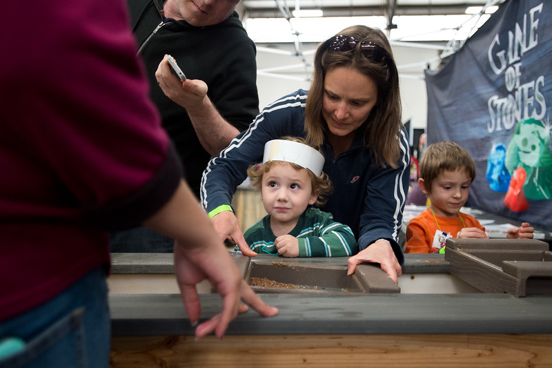 "Kristin Boes helps Maddock Myers, 2, sift through dirt to discover rocks while visiting the Game of Stones booth during the Rocky Mountain STEAM Fest at the Boulder County Fairgrounds in Longmont on Sunday.<br /> More photos:  <a href=""http://www.dailycamera.com"">http://www.dailycamera.com</a><br /> Autumn Parry/Staff Photographer<br /> May 1, 2016"