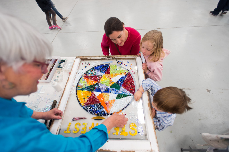"Artist Judy Batty shows Julie Layne and her children Felicia Layne, 6, and Corwin Layne, 3, how to glue pieces of glass to create a mosaic during the Rocky Mountain STEAM Fest at the Boulder County Fairgrounds in Longmont. Batty hopes the mosaics will be eventually hung in the Longmont Public Library.<br /> More photos:  <a href=""http://www.dailycamera.com"">http://www.dailycamera.com</a><br /> Autumn Parry/Staff Photographer<br /> May 1, 2016"