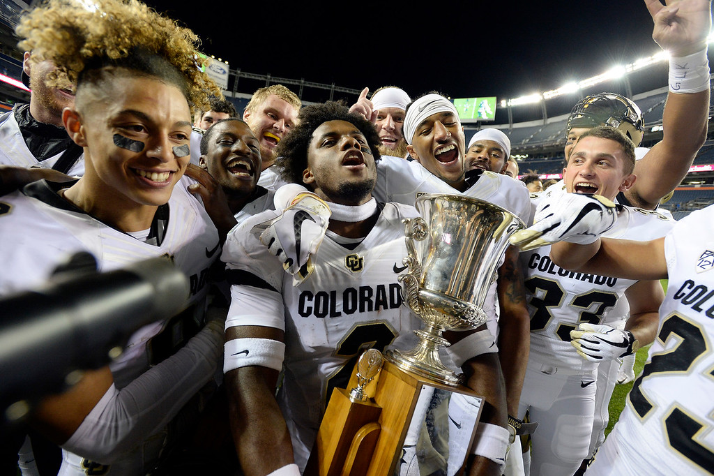 . DENVER, CO: August 31: Aaron Maddox, left, Ronnie Blackmon, left, and Derrion Rakestraw, celebrate the win with the Centennial Cup during the second half on August 31, 2018 at Bronco Stadium at Mile High. (photo by Cliff Grassmick/Staff Photographer).