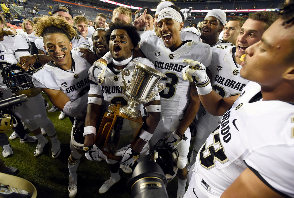 . DENVER, CO - AUGUST 31, 2018: University of Colorado players including Lavish Shenault Jr., at center, and K.D. Nixon hold the trophy after winning the Rocky Mountain Showdown football game against Colorado State University on Friday at Bronco\'s Stadium at Mile High in Denver. More photos: BoCoPreps.com (Photo by Jeremy Papasso/Staff Photographer)