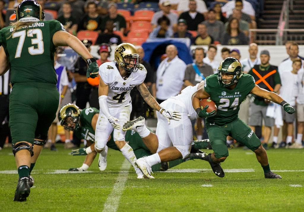 . Colorado State running back Izzy matthews (24) spins out of a Colorado tackle during the Rocky Mountain Showdown Friday evening August 31, 2018 at Sports Authority Field in Denver. (Michael Brian/For the Reporter-Herald)