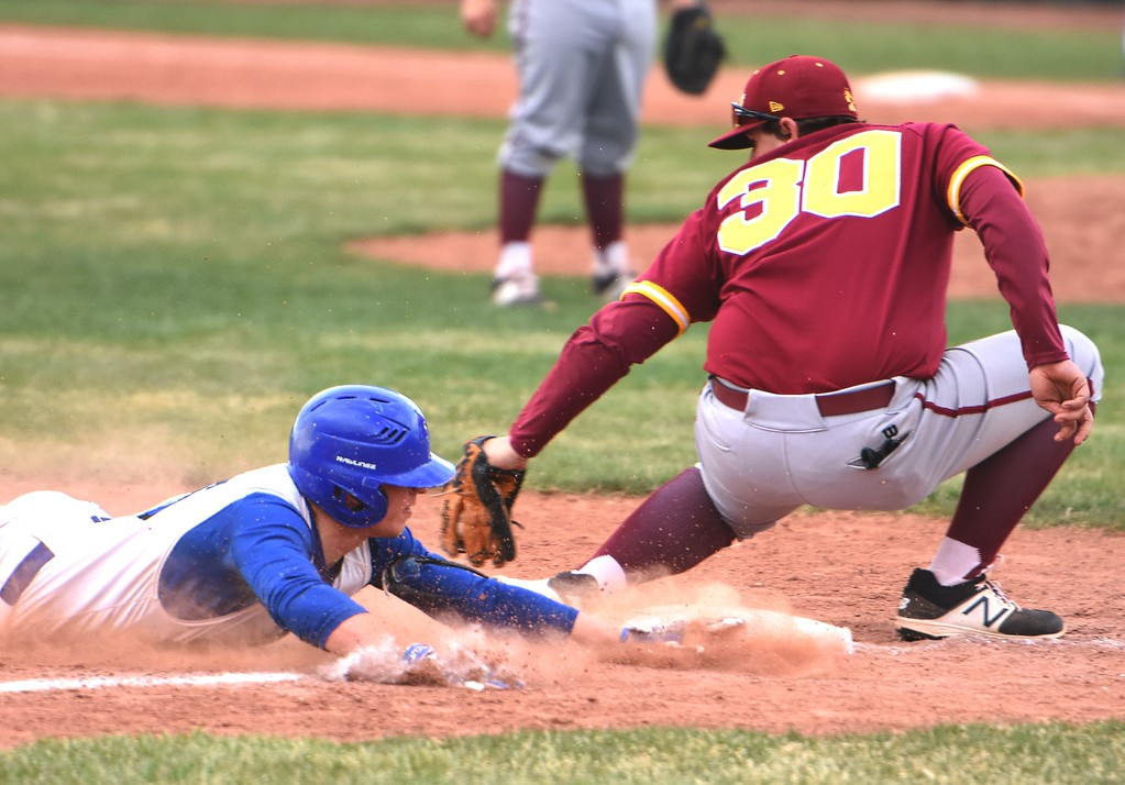 . Broomfield\'s Tanner Garner slides in just ahead of a tag from Rocky Mountain third baseman Cade Nelson during the Eagles\' game against Rocky Mountain on Thursday, April 12, at Broomfield High School.