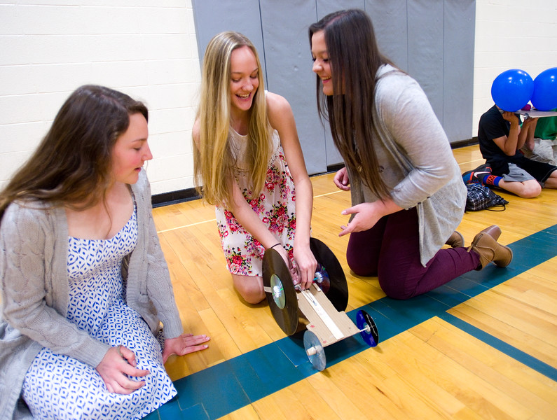 "From left to right, eighth graders Isabelle Parker, Addyson Huber and Libby Paznokas prepare their scooter, which has records for wheels and a rubber band around the axel to propel itself, for the race in the aux gym at Lyons Middle/Senior High School on Wednesday. The students built self powered scooters that follow Newton's Third Law of Motion.<br /> More photos:  <a href=""http://www.dailycamera.com"">http://www.dailycamera.com</a><br /> Autumn Parry/Staff Photographer<br /> May 25, 2016"