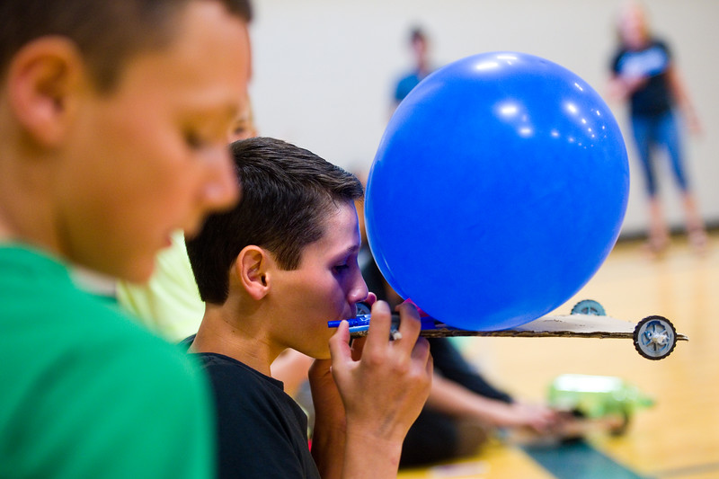 """Colton Bashor blows air into a balloon on his scooter, which uses air to propel itself, as he prepares for the race in the aux gym at Lyons Middle/Senior High School on Wednesday. The students built self powered scooters that follow Newton's Third Law of Motion.<br /> More photos:  <a href=""""http://www.dailycamera.com"""">http://www.dailycamera.com</a><br /> Autumn Parry/Staff Photographer<br /> May 25, 2016"""