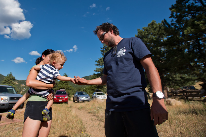 "Heather Lazrus holds her son Forrest Kehoe, 1, as he gives Charlie Schmidtmann a high five at the Betasso Preserve on Saturday morning. A search party gathered at the preserve to begin looking for Geno, a St. Bernard belonging to Charlie and Bretlyn Schmidtmann, who went missing during the Cold Springs Fire. <br /> More photos:  <a href=""http://www.dailycamera.com"">http://www.dailycamera.com</a><br /> (Autumn Parry/Staff Photographer)<br /> July 23, 2016"