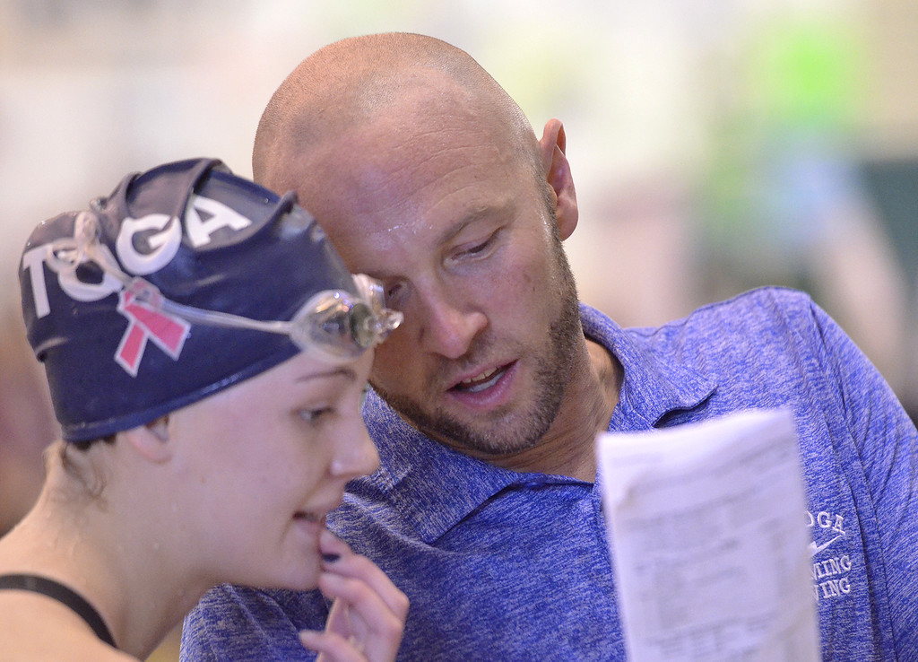 . Saratoga Springs Coach Josh Muldner shows a swimmer the results of her swim after the 200-yard freestyle final Saturday afternoon.