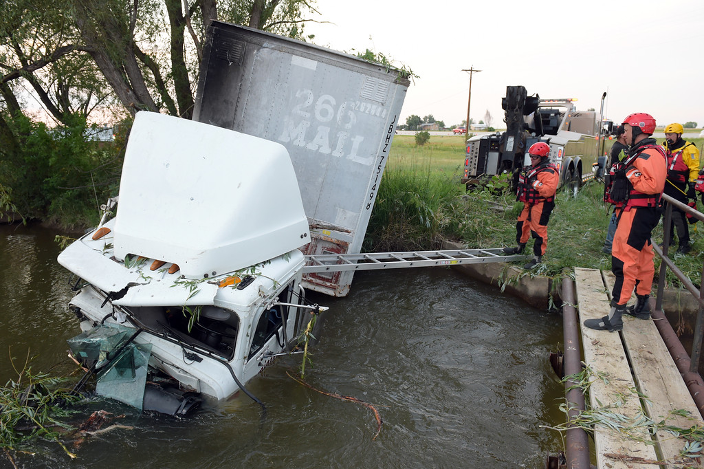 . Mountain View Fire Rescue swift water rescue team, assisted by the Longmont Emergency Unit water rescue team, at the scene of a crash involving a semi tractor trailer which ran into an irrigation ditch along U.S. 287 Thursday evening. Lewis Geyer/Staff Photographer July 06, 2017
