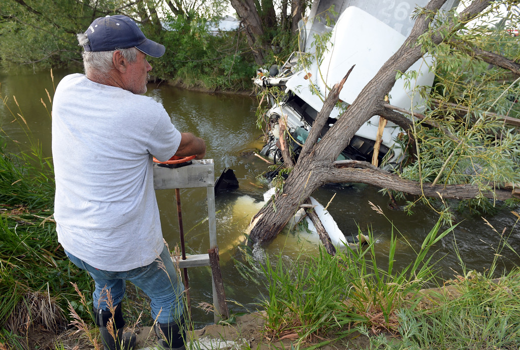 . Denny Melichar shuts the gate to the ditch leading to his farm at the scene of a crash involving a semi tractor trailer which ran into an irrigation ditch along U.S. 287 Thursday evening. Diesel fuel from the semi was leaking into the ditch. Lewis Geyer/Staff Photographer July 06, 2017