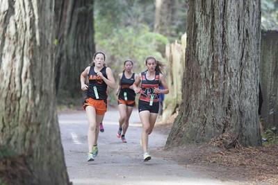Shaun Walker — The Times-Standard  Eventual winner and Arcata senior Chloe Pigg, left, 17, and second-place finsher Mack freshman Cece Ferreira, 14, race behind the Sequoia Park Zoo.