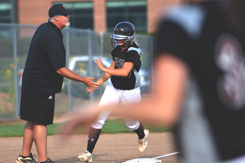 Head coach Ryan Beavers congratulates Silver Creek's Jetta Nannen as she rounds third base following teammate Lucy Scott's two-run home run during the Raptors' game against Mountain View on Tuesday at Mountain View High School in Loveland.
