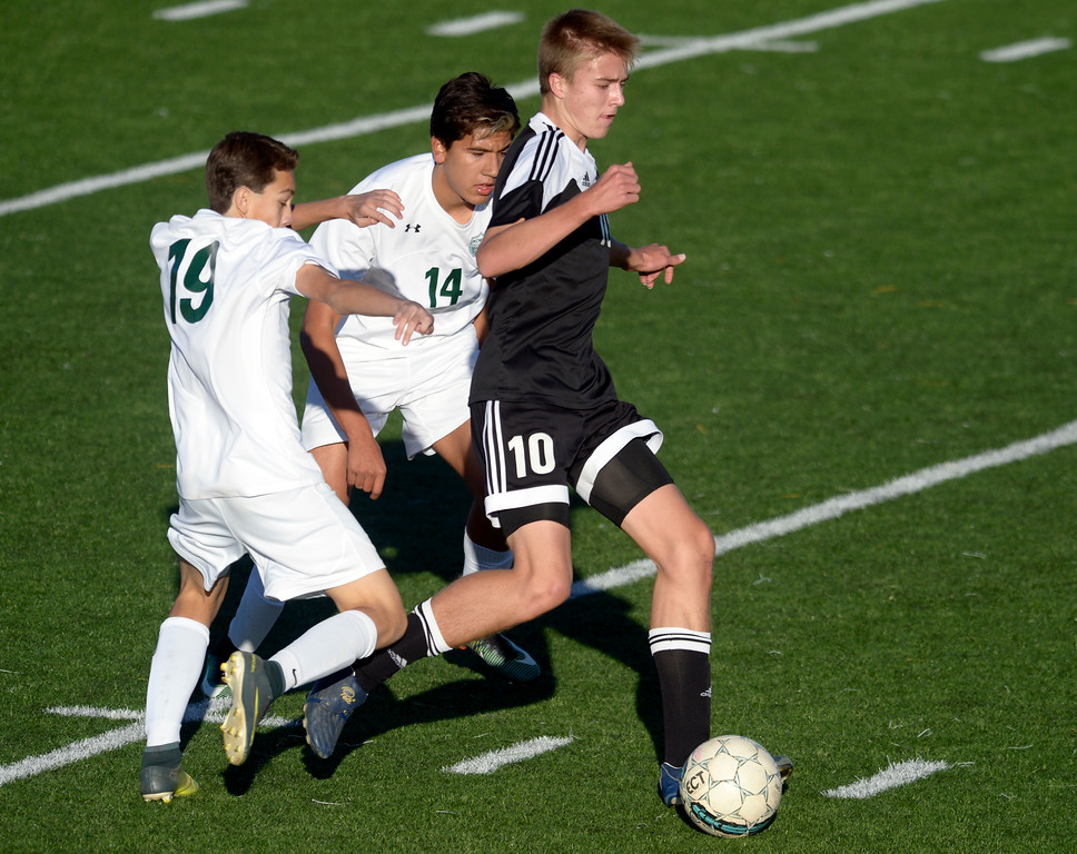 . Silver Creek\'s Jacob Van Ens keeps the ball away from Niwot\'s Brandon Morales and Manuel Tapia in the first half Tuesday evening at Erie High School. Niwot won 2-1. To view more photos visit bocopreps.com. Lewis Geyer/Staff Photographer Oct. 10, 62017