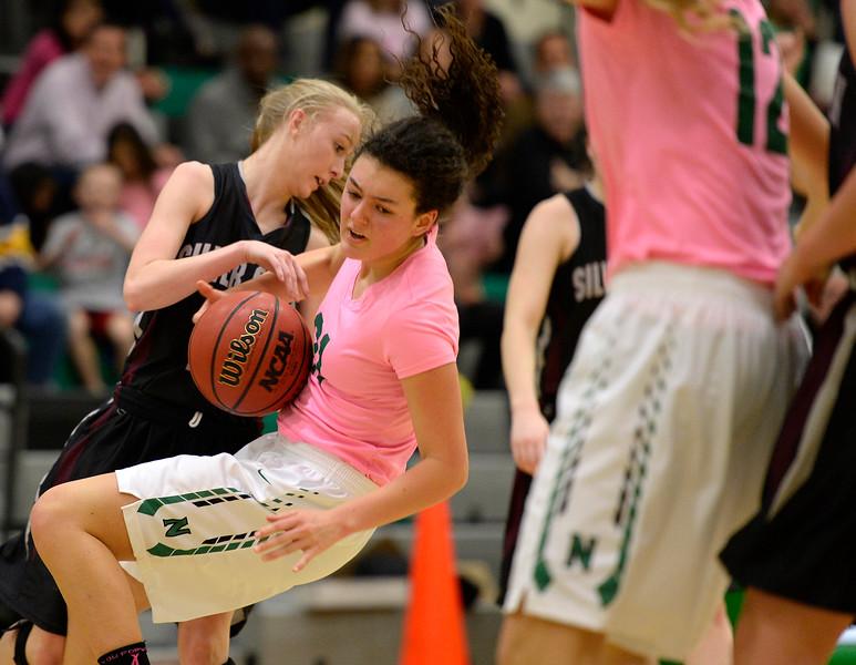 Silver Creek's Megan Harris fouls Niwot's Keena Strope in the second quarter at Niwot High School Friday night. (Staff Photographer Lewis Geyer) Jan. 29, 2016
