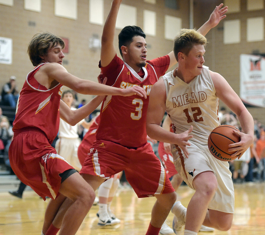 . Mead\'s Derek Edwards is coverd by Skyline\'s Brayden Blick and Camilo Martinez in the second quarter Tuesday night at Mead High School. To view more photos visit bocopreps.com. Lewis Geyer/Staff Photographer Feb. 06, 2018