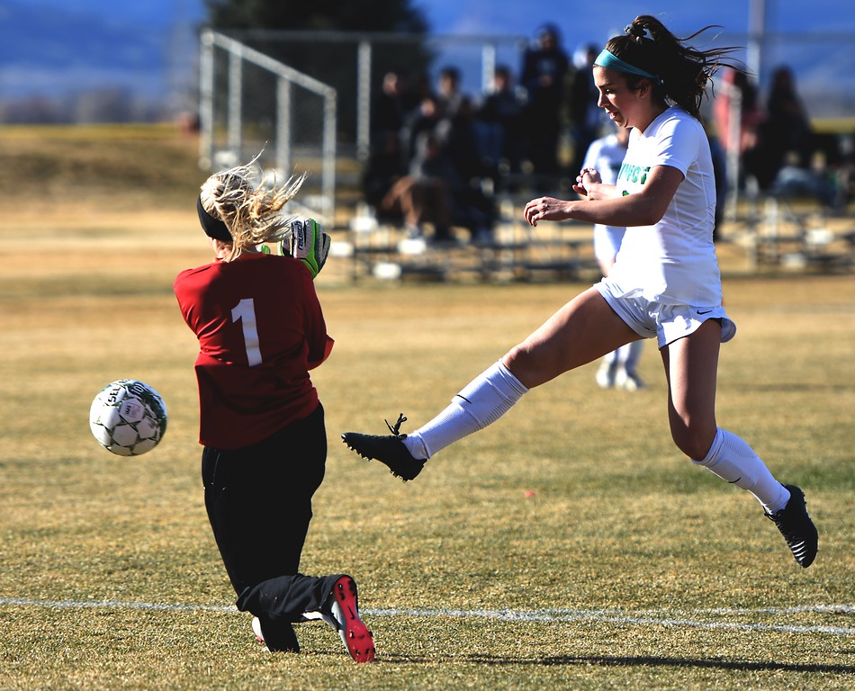 Niwot's Anna McCarthy, who leads the Cougars with six goals through three games, tries to get a shot past charging Skyline goalkeeper Kenna Meier on Tuesday, March 20, in Niwot.