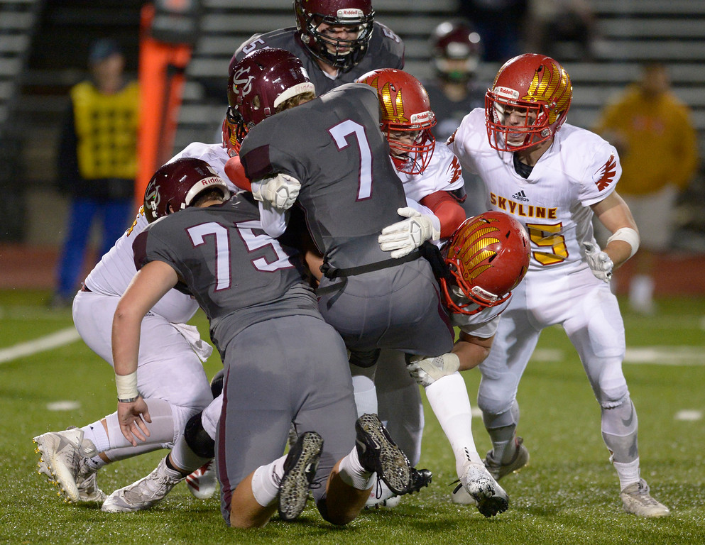 . LONGMONT, CO - OCTOBER 5: Silver Creek quarterback Carter Closson is driven back by Skyline defenders in the second quarter at Everly-Montgomery Field Oct. 05, 2018. (Photo by Lewis Geyer/Staff Photographer)