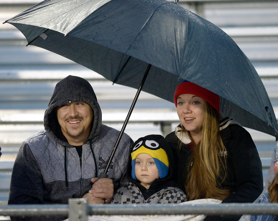 . LONGMONT, CO - OCTOBER 5: From left: Jesse Wisse, Jaxson Wisse, 3, and Kena Smith share an umbrella and a blanket during the wet weather at the start of the football game between Silver Creek and Skyline High Schools at Everly-Montgomery Field Oct. 05, 2018. (Photo by Lewis Geyer/Staff Photographer)
