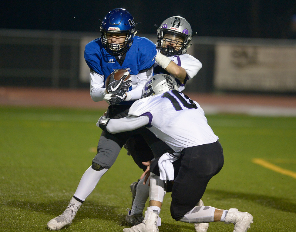 . Longmont\'s Sage Yazzie scores a touchdown against Skyview\'s Michael Vigil, 10, and Marcus Kemm in the first quarter Friday night at Everly-Montgomery Field. To view more photos visit bocopreps.com. Lewis Geyer/Staff Photographer Nov. 10, 2017