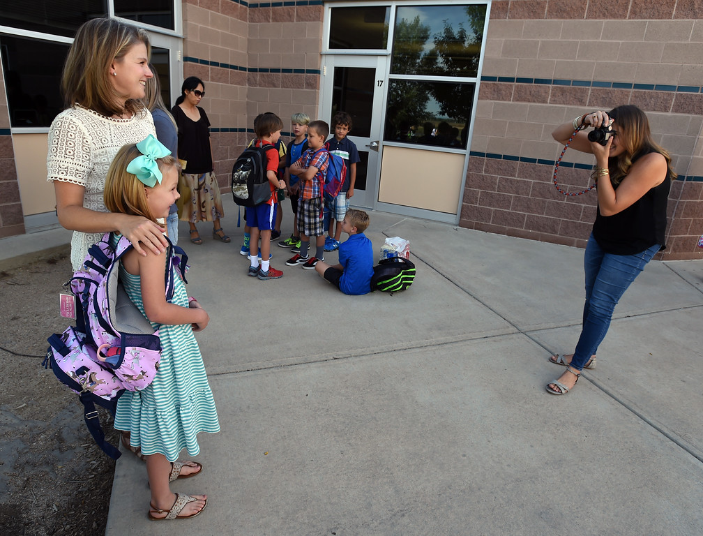 . Kristy Berger takes a photo for Courtney Ballagh and her daughter, Elery, during the first day of school at Blue Mountain Elementary in Longmont  in the St. Vrain Valley School District on Tuesday. For more photos, go to dailycamera.com.  Cliff Grassmick  Staff Photographer August 15, 2017