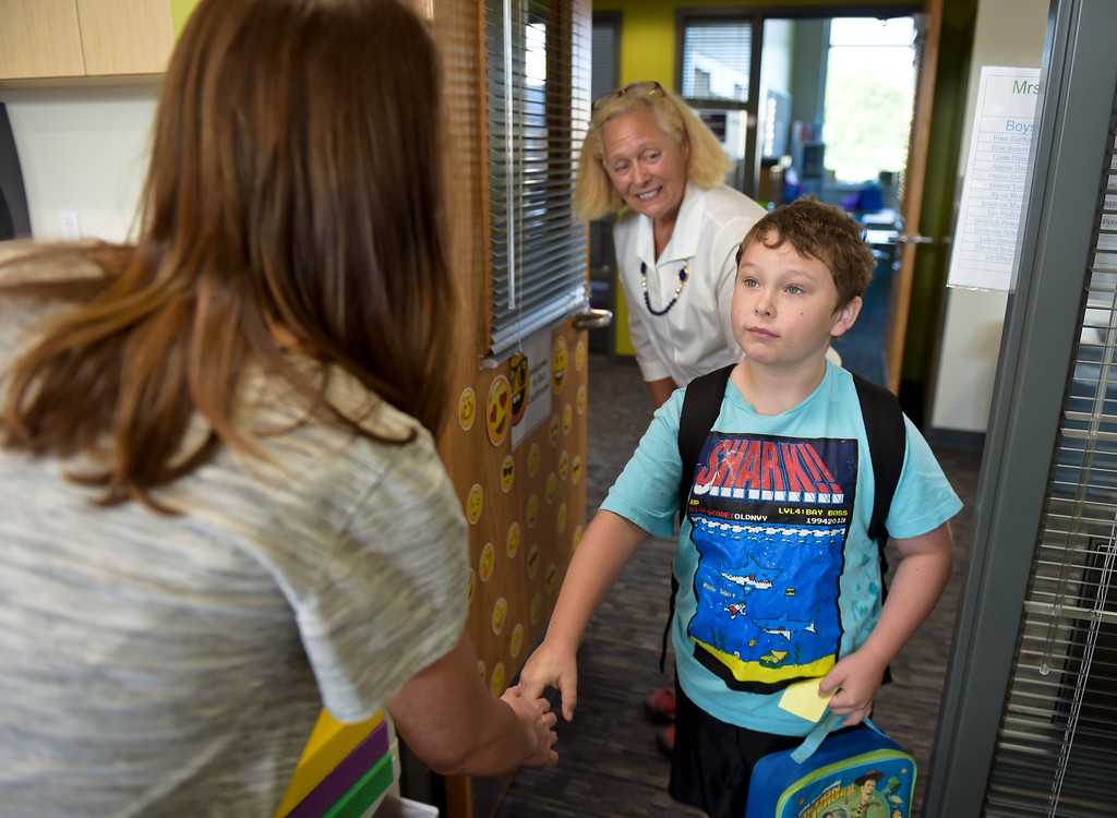 . Second grader Liam Dawson, 7, is introduced to his new teacher Acacia Nadeau, left, by paraeducator Cindy Bennett at Eagle Crest Elementary, 4444 Clover Basin Dr. Tuesday morning. To view more photos visit timescall.com. Lewis Geyer/Staff Photographer August 15, 2017