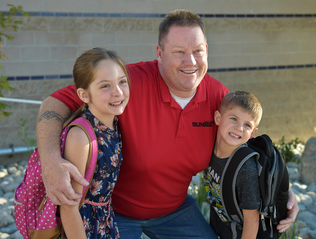 . Maddie Markowitz, 9, and Landon Gantenbein, 6, have their picture taken with their dad Steve Robertson before school starts at Eagle Crest Elementary, 4444 Clover Basin Dr. Tuesday morning. To view more photos visit timescall.com. Lewis Geyer/Staff Photographer August 15, 2017