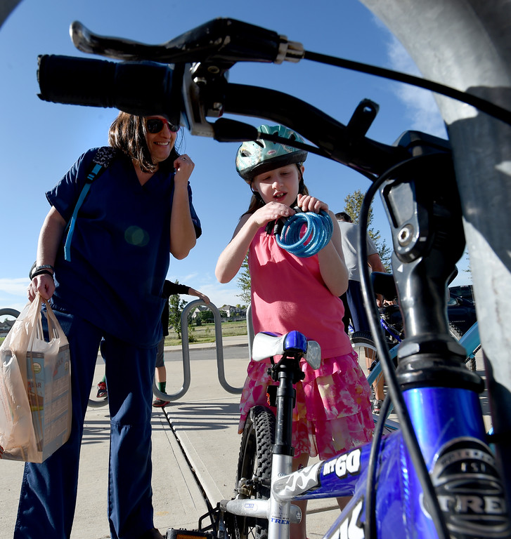 . Kaia Crouthamel locks up her bike with help from her mother, Karen, during the first day of school at Blue Mountain Elementary in Longmont  in the St. Vrain Valley School District on Tuesday. For more photos, go to dailycamera.com.  Cliff Grassmick  Staff Photographer August 15, 2017