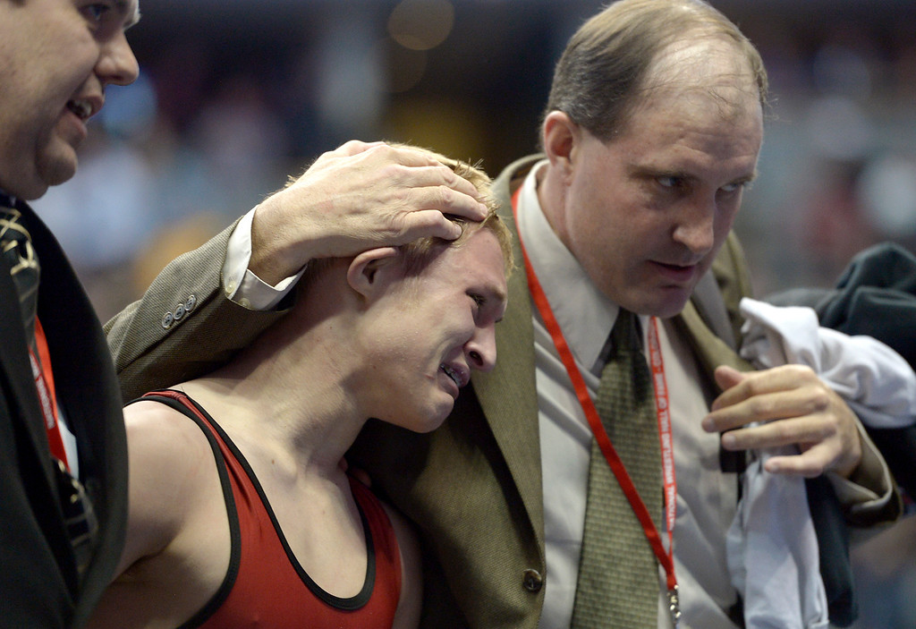 . Holly\'s Brendyn Nordyke is consoled after finishing second in the 2A 120 pound championship match during the state wrestling tournament at the Pepsi Center Saturday. To view more photos visit bocopreps.com. Lewis Geyer/Staff Photographer Feb. 18, 2017