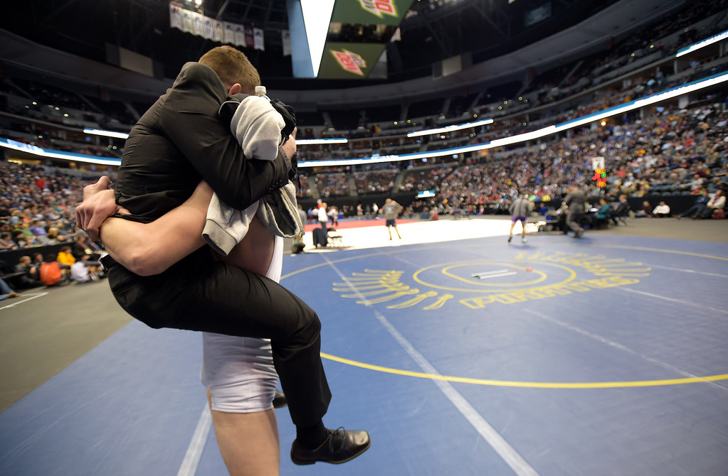 . Lyons\' Keegan Bean lifts his coach Brandon Lohr off the mat after Bean won the 2A 182 pound final during the state wrestling tournament at the Pepsi Center Saturday. To view more photos visit bocopreps.com. Lewis Geyer/Staff Photographer Feb. 18, 2017