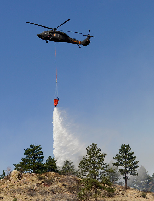 . A Colorado National Guard helicopter makes water drops on the fire in Sunshine Canyon in Boulder on Sunday. More photos: DailyCamera.com. Matthew Jonas/Staff Photographer March 19,  2017
