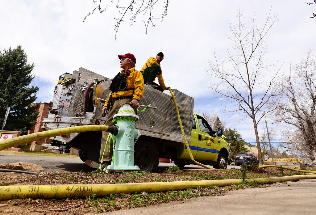 . From left: Allenspark Fire Protection District volunteer firefighters Clifton DeWitt and Brad Ready fill a brush truck with water before heading back up the fire in Sunshine Canyon west of Boulder on Sunday. More photos: DailyCamera.com. Matthew Jonas/Staff Photographer March 19,  2017