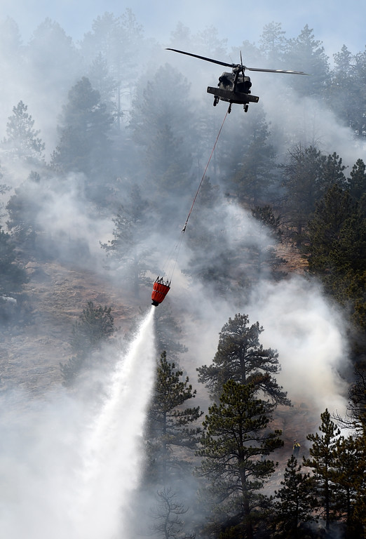 . A helicopter drops water on the fire as crews battle the Sunshine Fire in the Sunshine canyon area of Boulder, Colo. on Sunday, March 19. For more photos of the Sunshine Fire go to www.dailycamera.com Jeremy Papasso/ Staff Photographer/ March 19, 2017