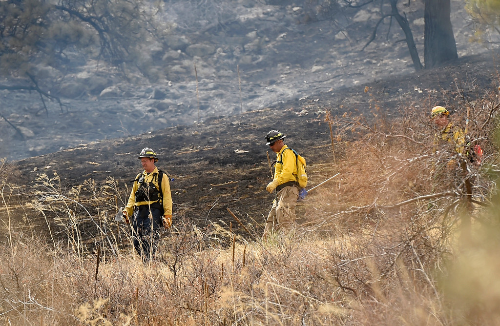 . Firefighters head back to the truck as crews battle the Sunshine Fire in the Sunshine canyon area of Boulder, Colo. on Sunday, March 19. For more photos of the Sunshine Fire go to www.dailycamera.com Jeremy Papasso/ Staff Photographer/ March 19, 2017