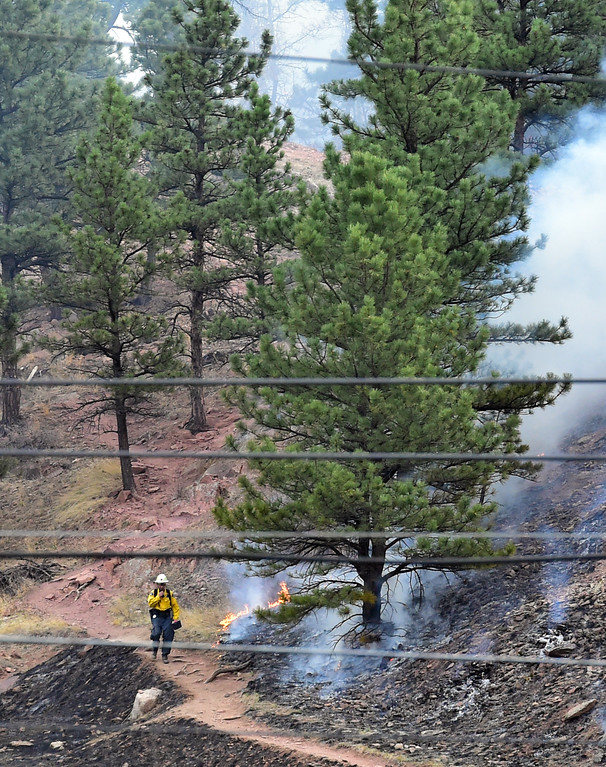 . A firefighter walks near the flames on the south side of the Sunshine Fire near Boulder Canyon west of Boulder on Sunday  Paul Aiken Staff Photographer March 19 2017