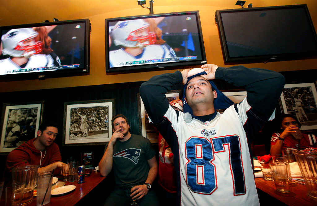 . Milind Kamdar reacts at a Boston bar to a missed catch by New England Patriots quarterback Tom Brady while watching the first half of the NFL Super Bowl 52 football game between the Patriots and the Philadelphia Eagles in Minneapolis, Sunday, Feb. 4, 2018. (AP Photo/Steven Senne)