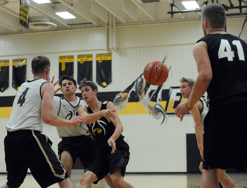 . Thompson Valley\'s Justin Wiersema passes to teammate Joey Shaffer (41) next to the defense of teammates Adrian Juarez, middle left, and Paul Pomerleau during a recent practice at TVHS.