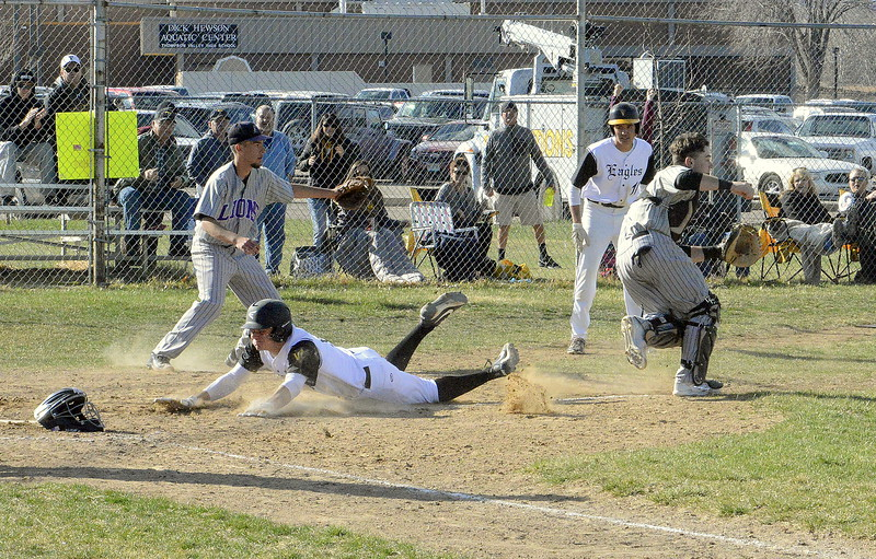 Thompson Valley's Cameron Nellor slides into home at Mountain View catcher Mike Felton chases down an errant throw during Monday's game at Constantz Field. The Eagles won 16-7. (Mike Brohard/Loveland Reporter-Herald)