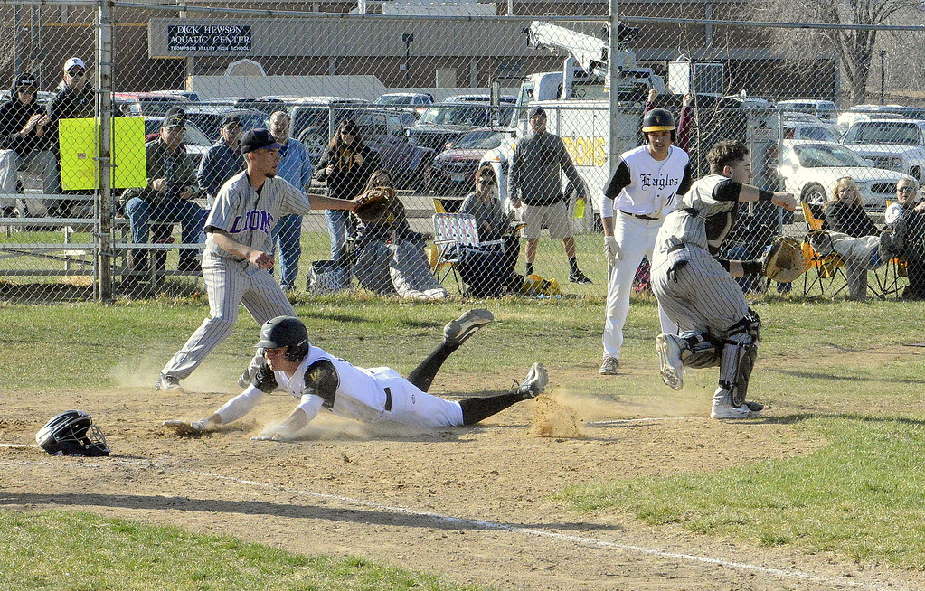 . Thompson Valley\'s Cameron Nellor slides into home at Mountain View catcher Mike Felton chases down an errant throw during Monday\'s game at Constantz Field. The Eagles won 16-7. (Mike Brohard/Loveland Reporter-Herald)