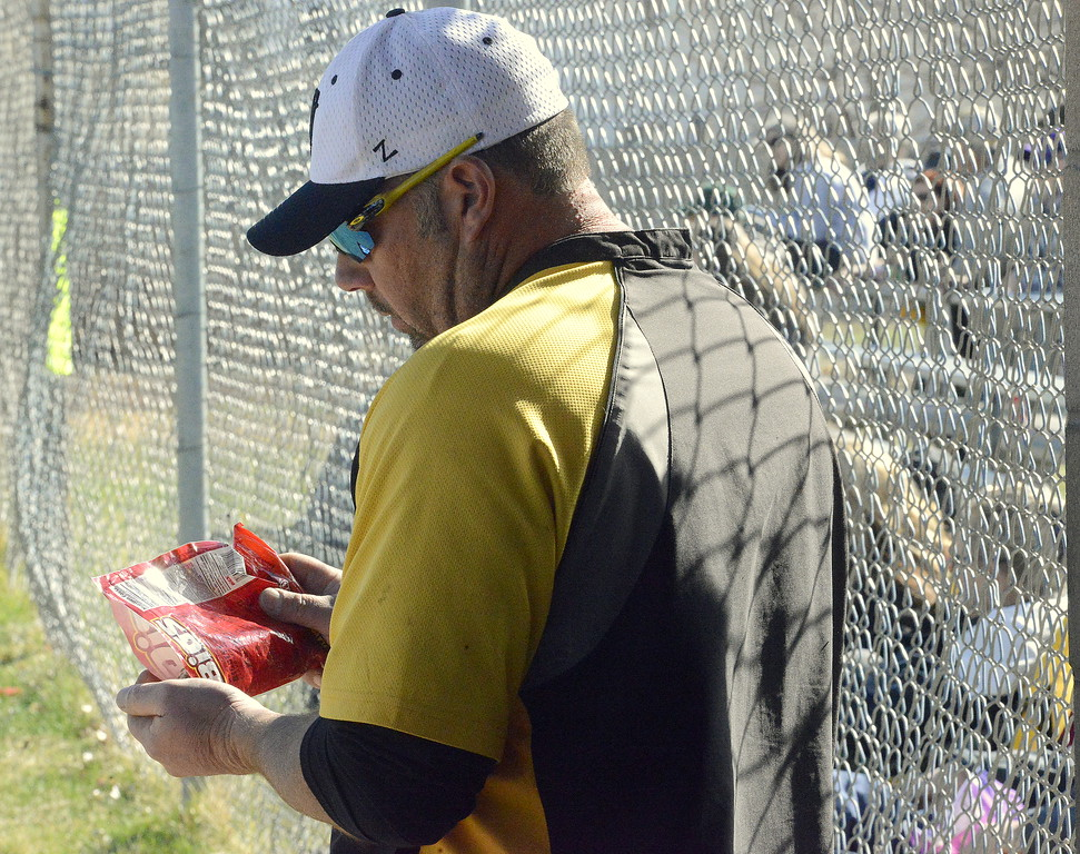 . Thompson Valley assistant coach Chad Raabe gets a handful of sunflower seeds in the dugout during Monday\'s game with Mountain View at Constantz Field. (Mike Brohard/Loveland Reporter-Herald)