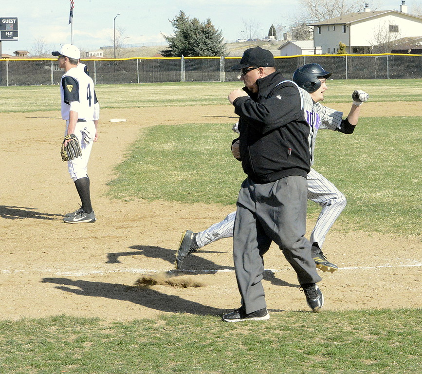 . The umpire tries to get out of the way as Mountain View\'s Brexton Butcher cuts third and heads for home to score on T.J. Mendoza\'s second-inning double in Mounday\'s game with Thompson Valley at Constantz Field. (Mike Brohard/Loveland Reporter-Herald)