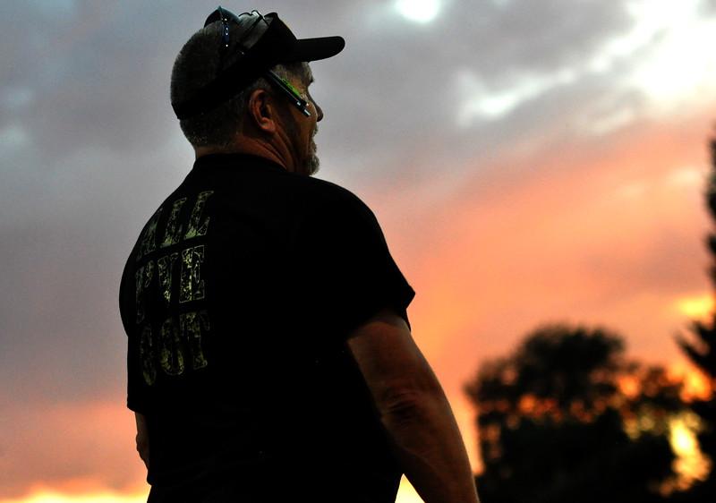 Thompson Valley softball coach Bryon Rutherford looks on as the sun sets over Centennial Park on Friday Aug. 25, 2017 against Berthoud. (Cris Tiller / Loveland Reporter-Herald)