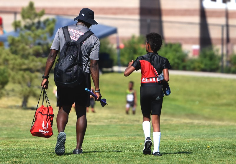 CDm Elite and Skyline High coach James Davis (left) walks with Miley Davis between events during the USATF Region 10 Championships on Saturday at Legacy Stadium in Aurora.