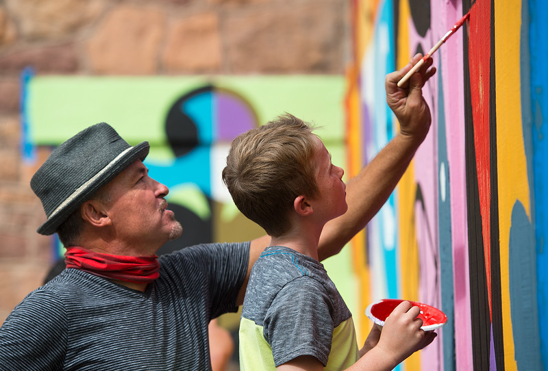 "Rafael López helps Jack Wendell, 9, paint the mural in replacement of the BotStories mural on 13th St. and Arapahoe Ave., in Boulder on Friday.<br /> More photos:  <a href=""http://www.dailycamera.com"">http://www.dailycamera.com</a><br /> (Autumn Parry/Staff Photographer)<br /> September 30, 2016"