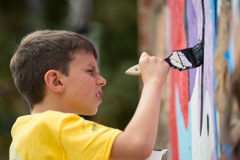 "Sheamus Murphy, 9, a fourth grader from University Hill Elementary, helps paint a mural created by internationally renowned artist Rafael López, in replacement of the BotStories mural on 13th St. and Arapahoe Ave., in Boulder on Friday.<br /> More photos:  <a href=""http://www.dailycamera.com"">http://www.dailycamera.com</a><br /> (Autumn Parry/Staff Photographer)<br /> September 30, 2016"