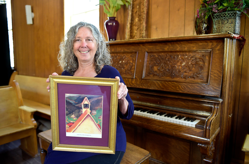 . WARD, CO - SEPTEMBER 13, 2018: Becky Martinek holds a copy of the Georgia O\'Keefe painting which features the belltower of Union Congregational Church of Ward Sept. 13. A groundbreaking will take place Sunday to herald a $50,000 renovation for the 122-year-old church, the same one whose belltower is featured in a painting by Georgia O\'Keefe.(Photo by Lewis Geyer/Staff Photographer)