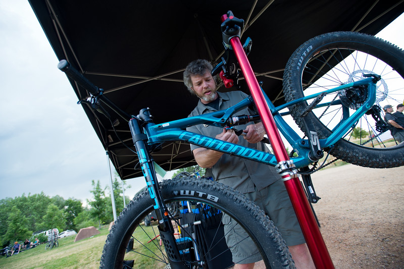"Joey Gallagher, a tech specialist II with REI, makes final adjustments to a bike for a free demo, as part of Valmont Bike Park's fifth anniversary celebration, on Saturday.<br /> More photos:  <a href=""http://www.dailycamera.com"">http://www.dailycamera.com</a><br /> (Autumn Parry/Staff Photographer)<br /> June 11, 2016"