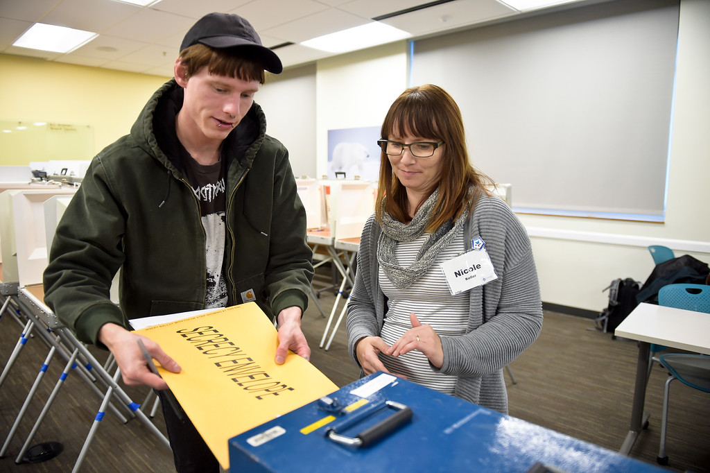 . LONGMONT, CO - NOVEMBER 5: Election judge Nicole Keller assists Jaran Berg with putting his ballot in the ballot box at the Boulder County St. Vrain Community Hub Nov. 5, 2018. (Photo by Lewis Geyer/Staff Photographer)