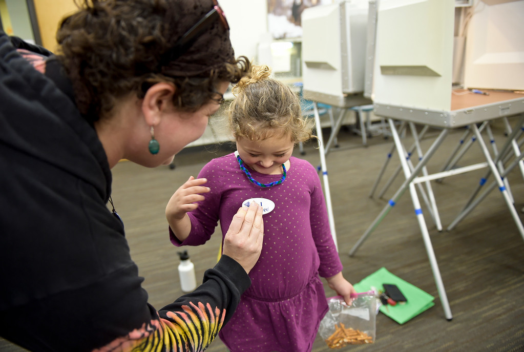 ". LONGMONT, CO - NOVEMBER 5: Rosemary Ghiasi-Henrichon, 4, gets her own ""I Voted\"" sticker from her mother Elizabeth Henrichon after Elizabeth voted at the Boulder County St. Vrain Community Hub Nov. 5, 2018. \""It\'s my first time voting in 10 years,\"" Elizabeth Henrichon said. (Photo by Lewis Geyer/Staff Photographer)"