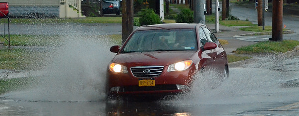 KYLE MENNIG - ONEIDA DAILY DISPATCH A car drives east on Lenox Avenue following a storm in the City of Oneida on Wednesday, July 13, 2016.